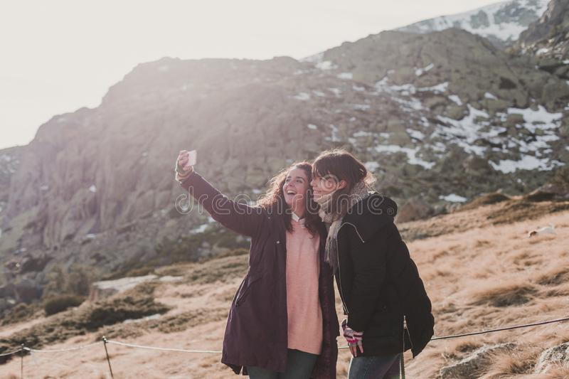 Two successful hiker woman friends enjoy the view on mountain peak. Happy backpackers in nature taking pictures with mobile phone royalty free stock photos