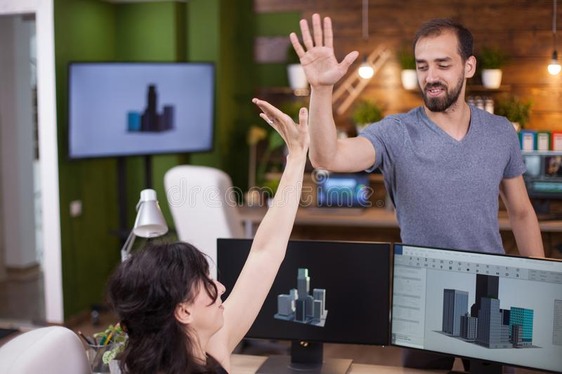 Two successful young business partners give a hi5 to each other royalty free stock image
