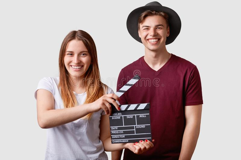 Two successful young female and male famous producers or directors hold film clapper, participate in shooting film, have joyful ex royalty free stock photos