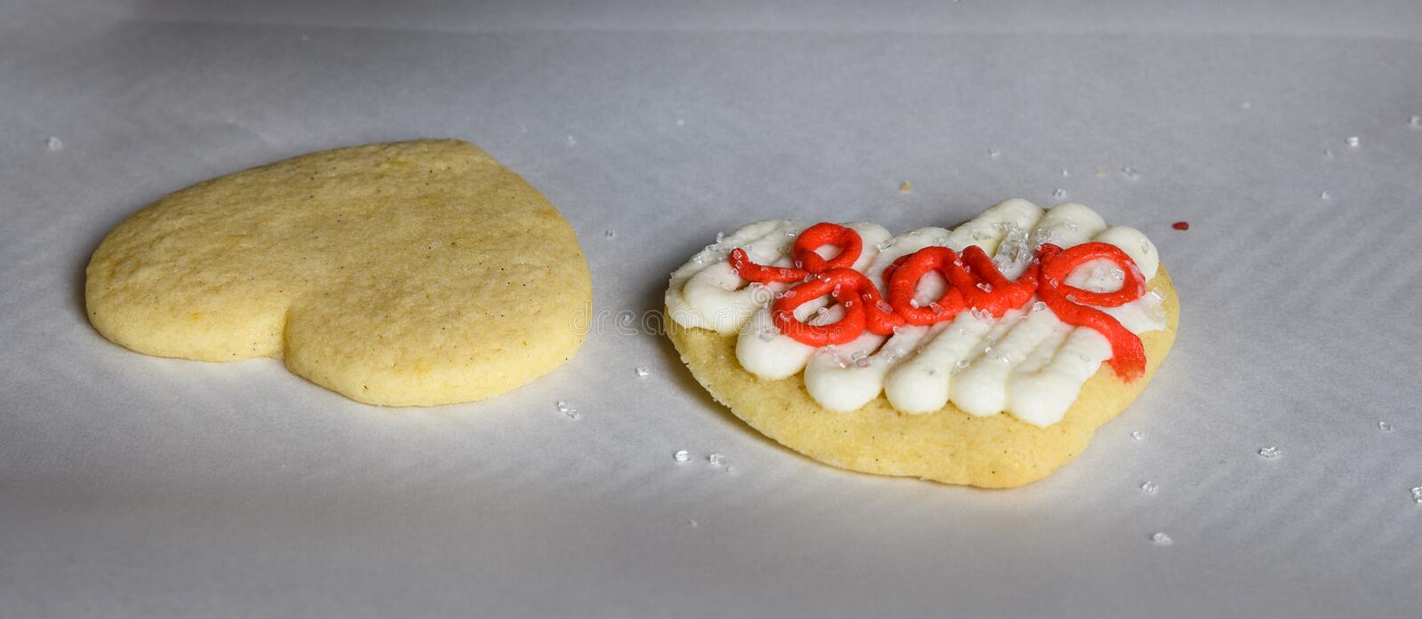Two sugar cookies on parchment paper covered cookie sheet, one decorated and one not stock image