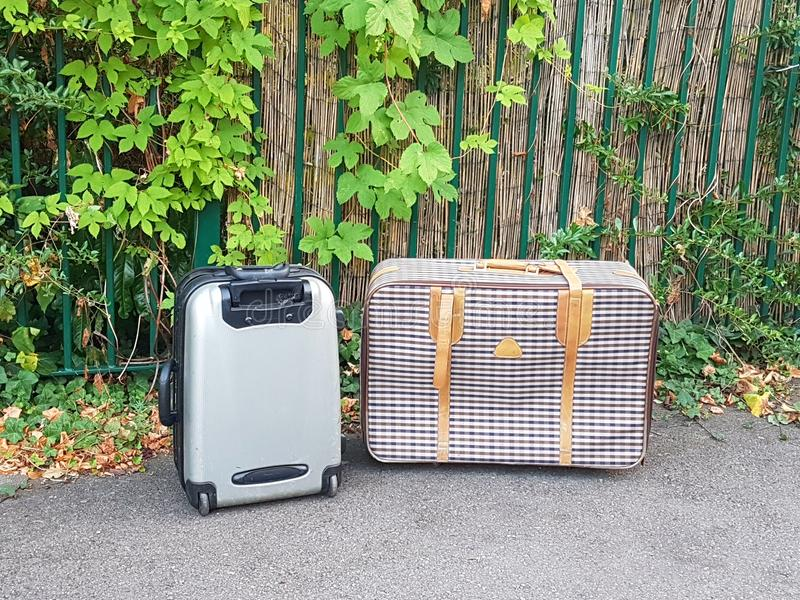 Two suitcases. Two different styles of suitcase outside on the ground royalty free stock images
