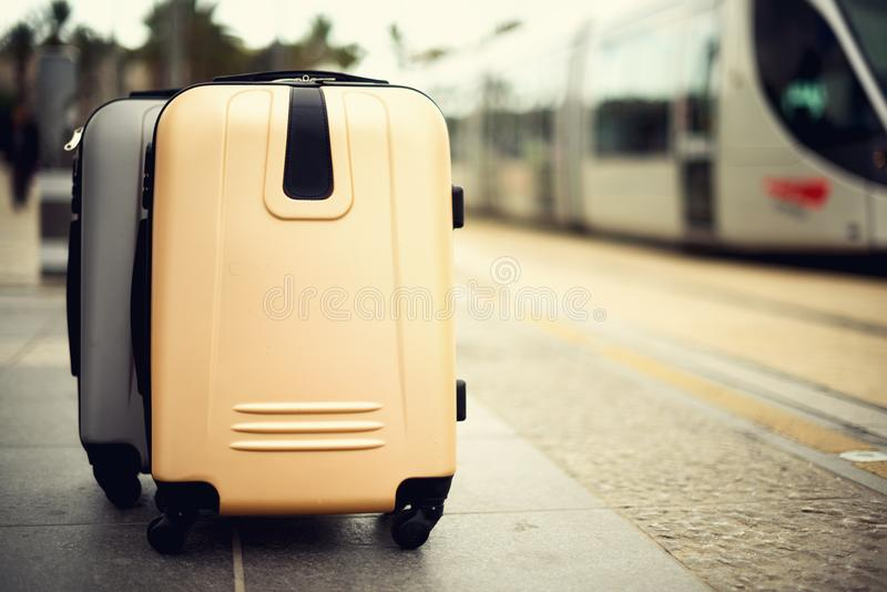 Two suitcases standing on railway station against city train. Vacation and travel concept. Citypass Light Rail in. Jerusalem. Copy space, selective focus stock photos