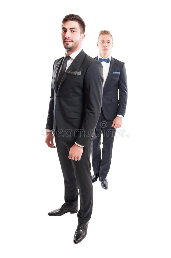Two suited male models wearing necktie and bowtie royalty free stock images