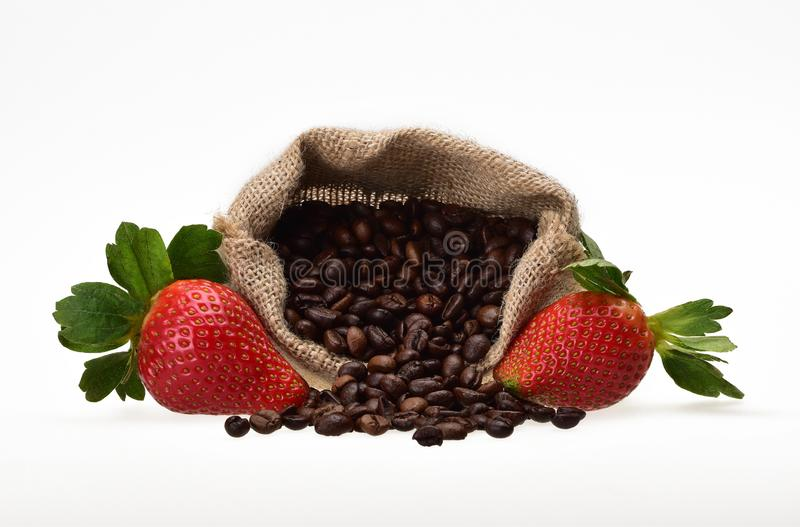 Two summer berries of strawberries with green petals and a canvas bag with roasted beans of aromatic coffee. On a neutral white background stock photo