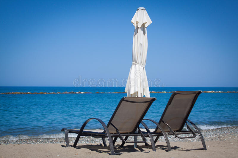 Two sun loungers. On the beach royalty free stock images