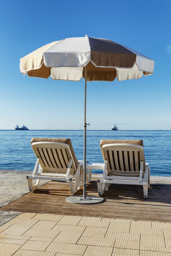 Two sun loungers under an umbrella overlooking the sea. Relax and pleasure. Beautiful view. stock photography