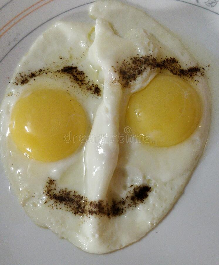 Two sunny side up fried eggs cooked like a human face with two eyes with egg yolks, eyebrows and lips are made and nose royalty free stock images