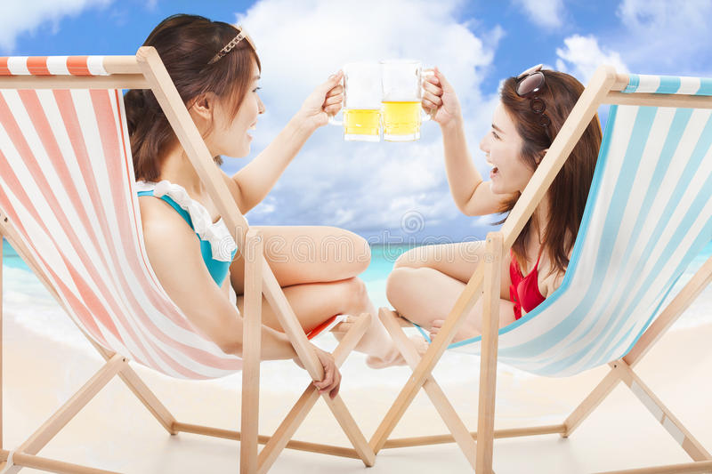 Two sunshine girls holding beer cheers on a beach chair stock images