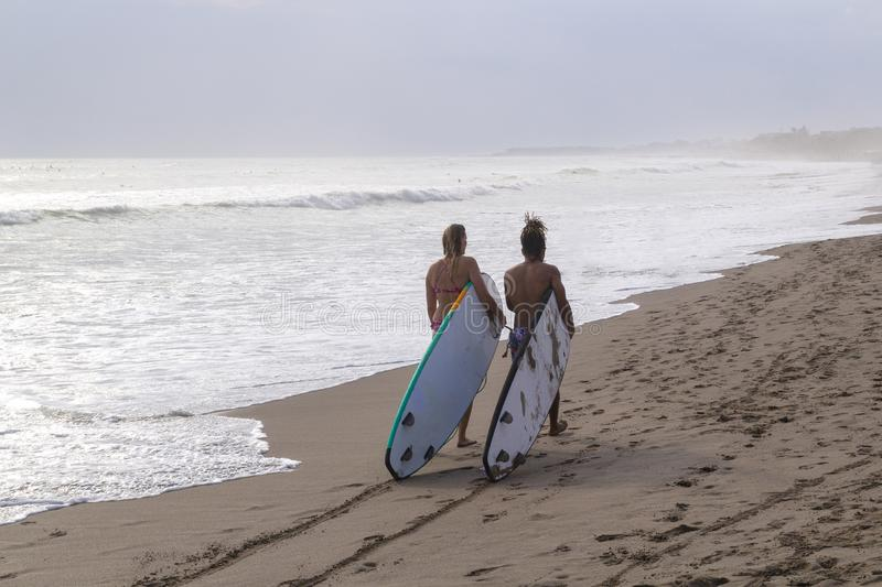 Two surfers couple go on the ocean beach with longboards in hand stock photos
