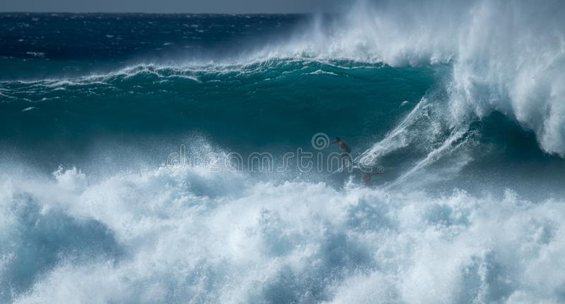 Two surfers sharing the giant wave at the famous Waimea Bay stock photo