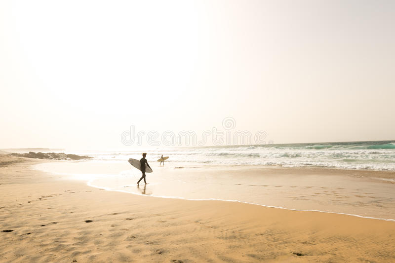 Two surfers walking to waves on an empty beach royalty free stock photo