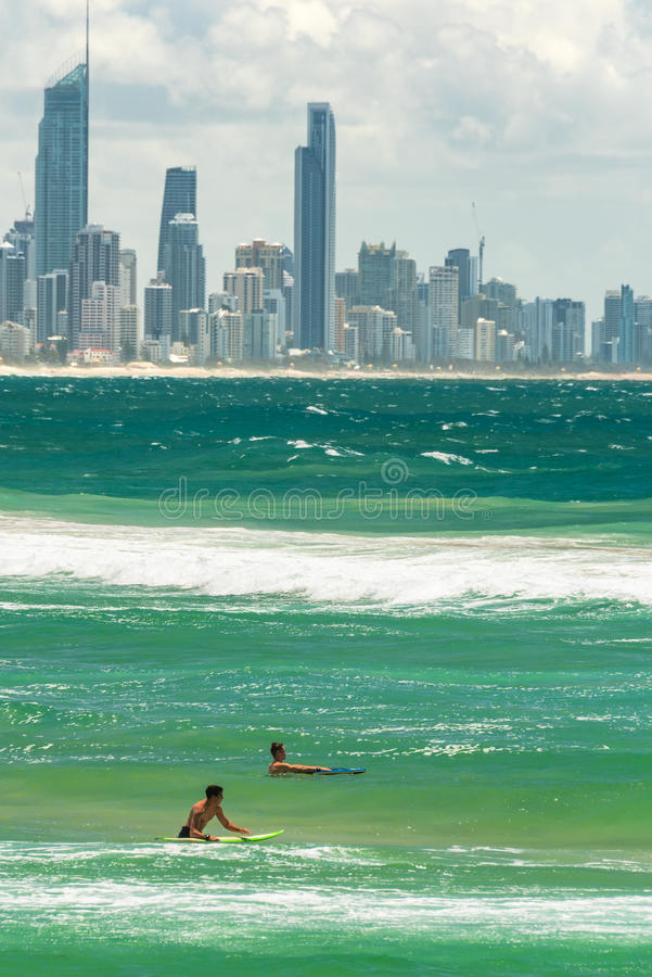 Two surfers in water with Gold Coast cityscape on background stock photo