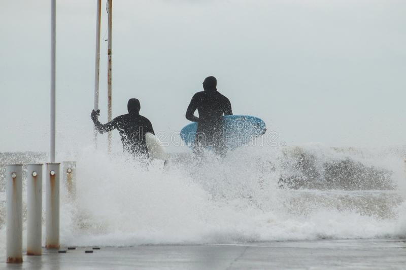 Two  surfers in wetsuits with surfboard on a city pier amid powerful waves in Australia. royalty free stock photography