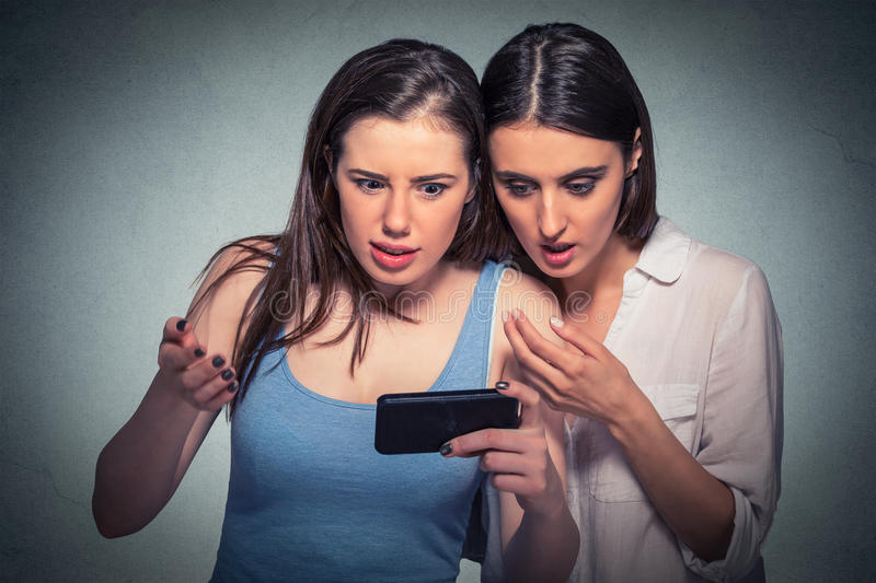 Two surprised girls looking at cell phone discussing latest gossip news. Flabbergasted at what they see gray background royalty free stock photos