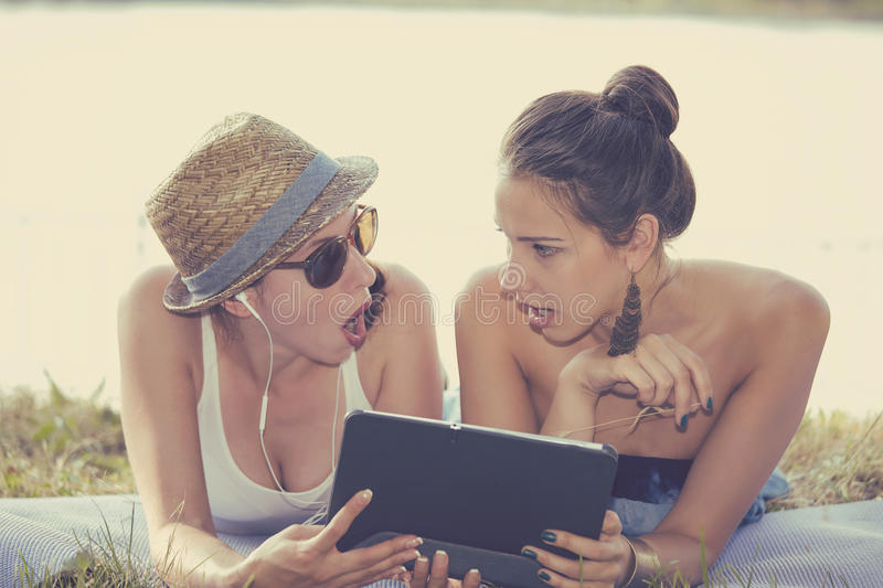 Two surprised girls looking at pad discussing latest gossip news. Closeup portrait two surprised girls looking at pad discussing latest gossip news. Young stock images