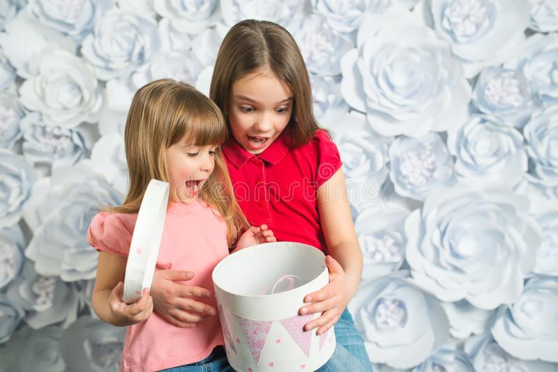 Two surprised little girls open a gift royalty free stock images