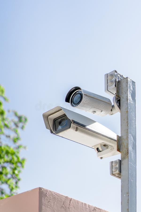Two surveillance cameras on a pole against a blue sky stock photography
