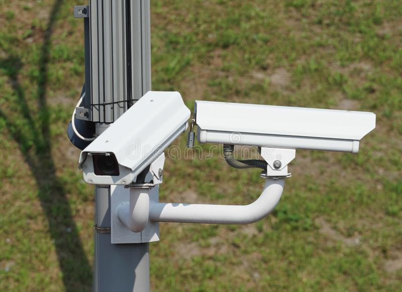 Surveillance cameras. Two surveillance cameras in an urban area to maintain security and to observe the surroundings stock photography