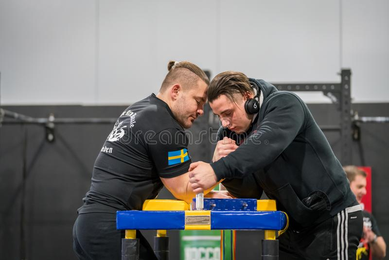 Two Swedish arm wrestlers in a friendly fight. STOCKHOLM, SWEDEN - JANUARY 13, 2018: Profile view of two Swedish male arm wrestlers warming up at the event Arm royalty free stock images