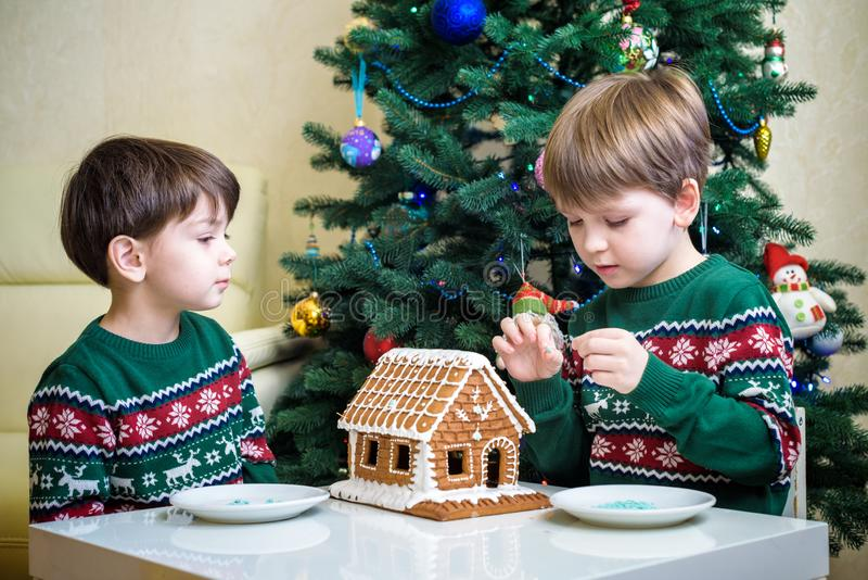 Two sweet boys, brothers, making gingerbread cookies house, decorating at home in front of the Christmas tree, child playing and royalty free stock photography