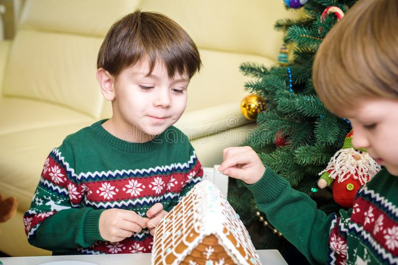 Two sweet boys, brothers, making gingerbread cookies house, decorating at home in front of the Christmas tree, child playing and stock image