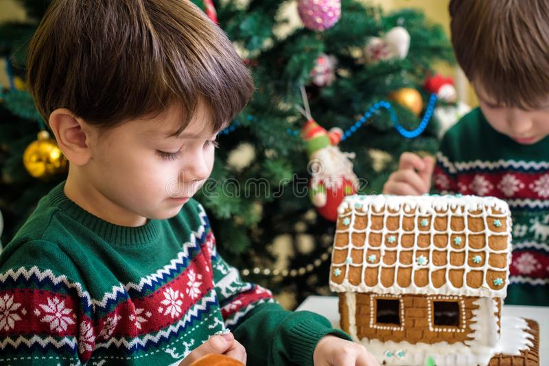 Two sweet boys, brothers, making gingerbread cookies house, decorating at home in front of the Christmas tree, child playing and stock photos