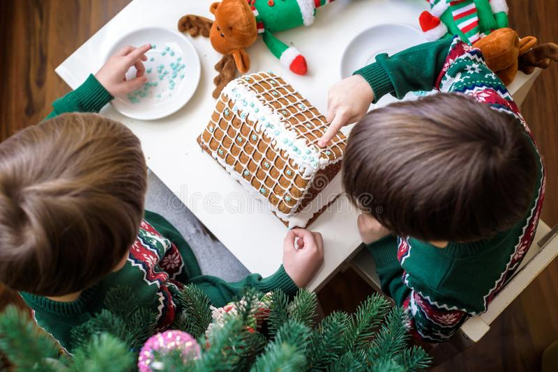 Two sweet boys, brothers, making gingerbread cookies house, decorating at home in front of the Christmas tree, child playing and stock photo