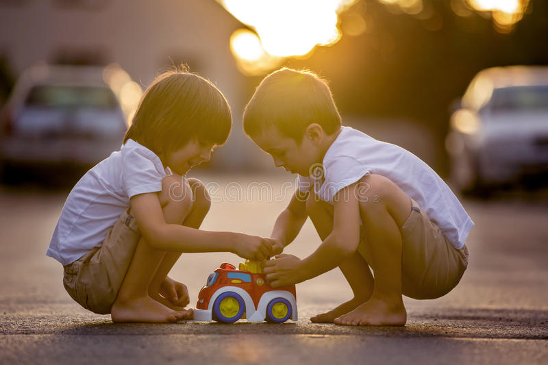 Two sweet children, boy brothers, playing with car toys on the s royalty free stock images