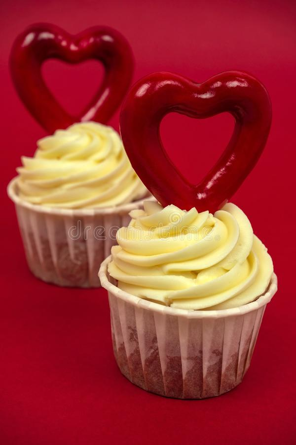 Sweet cupcakes with butter cream decorated with big red heart on a red background. Two sweet cupcakes with butter cream decorated with big red heart on a red royalty free stock image