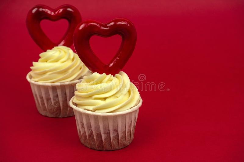 Sweet cupcakes with butter cream decorated with big red heart on a red background. Two sweet cupcakes with butter cream decorated with big red heart on a red royalty free stock images