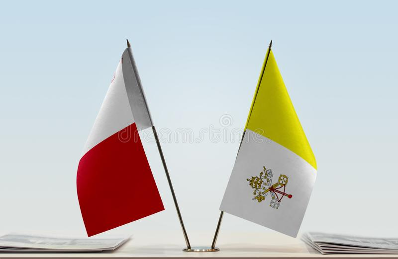 Flags of Malta and Vatican. Two table flags of Malta and Vatican royalty free stock photography