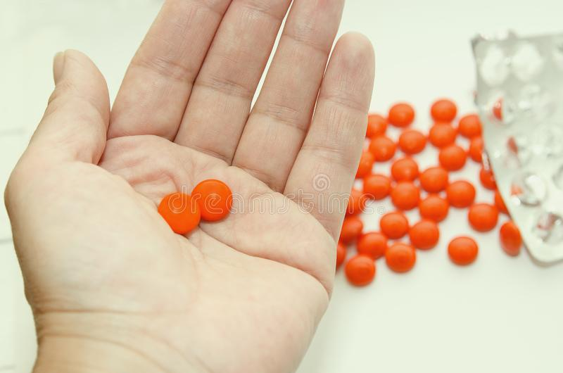 Two tablets in an orange shell lie on the palm of your hand. Close-up stock images