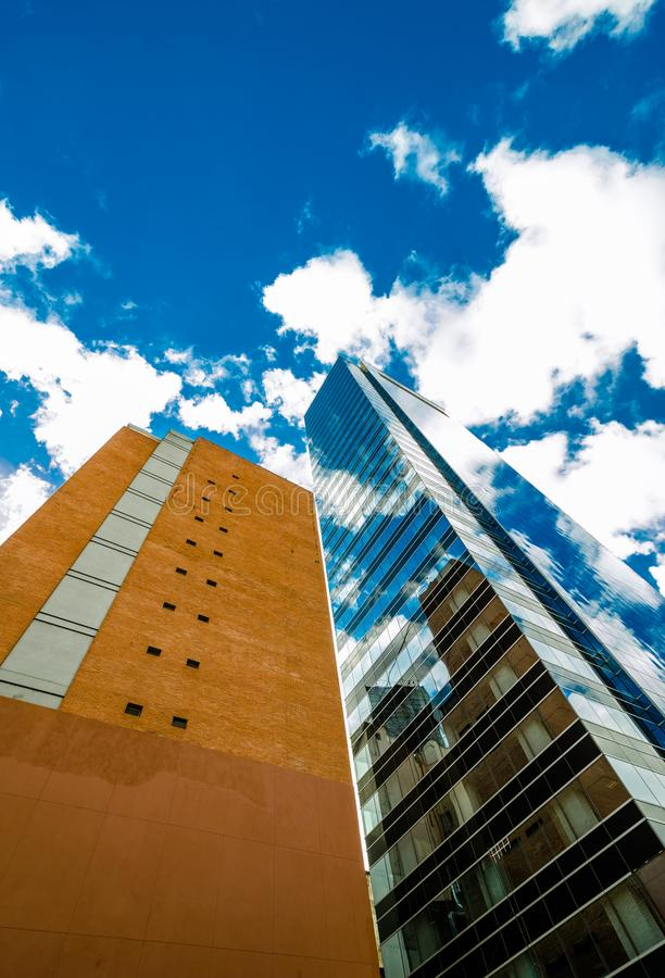 Two tall buildings with reflection against blue sky with beautiful clouds royalty free stock photo