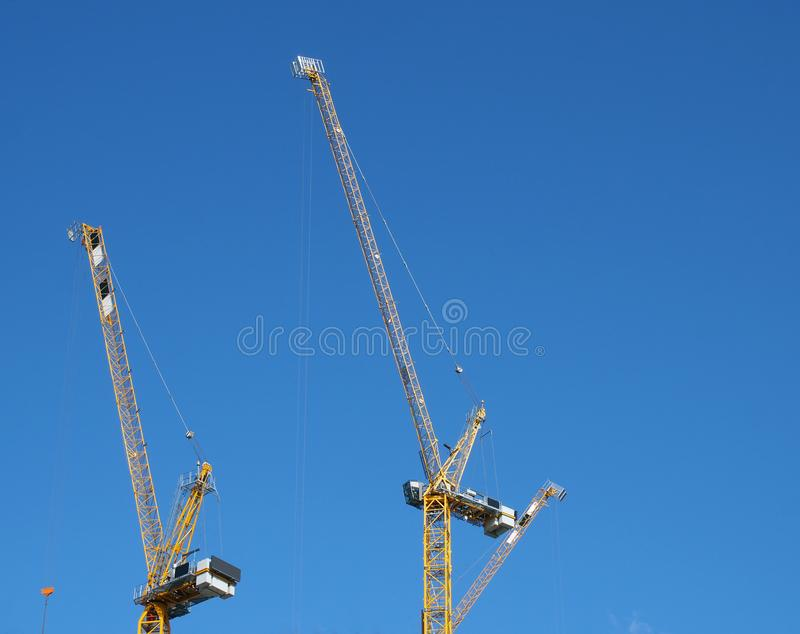 Two tall yellow construction cranes working against a blue sky stock photography