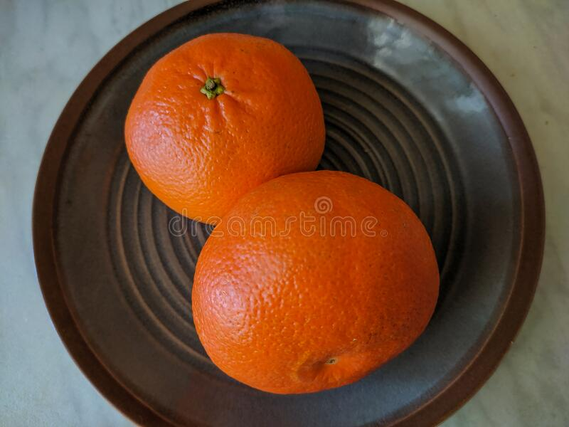 Two tangerines on the plate. View from above royalty free stock images