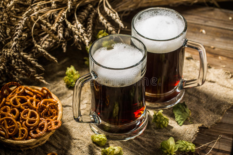Two tankard beer with wheat and hops , basket of pretzels. On wooden table stock photography