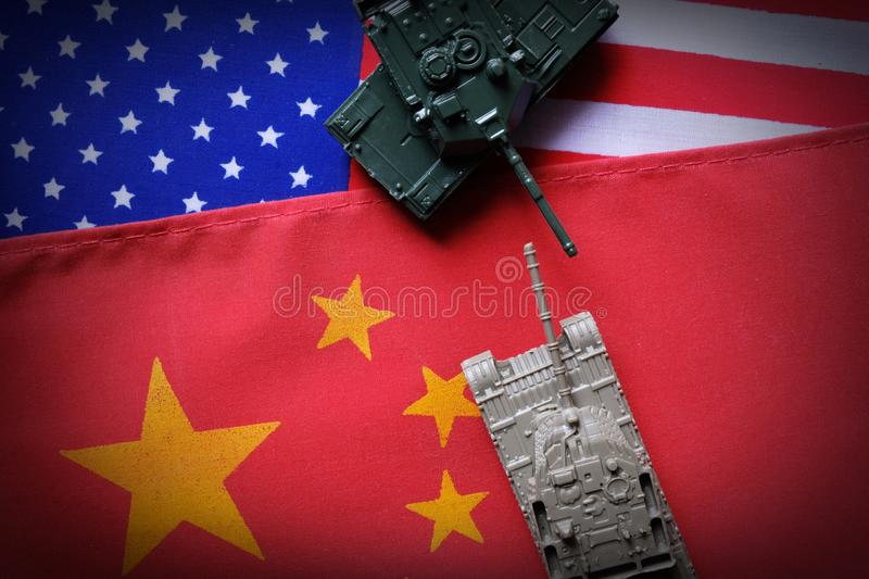 Two tanks face to face on USA and China national flag background. Refer to conflict between two countries is heating up. China and. USA trade war concept. Copy stock image