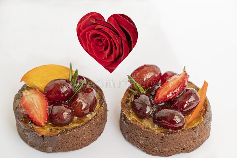 Two tasty chocolate cakes with icing fruits and berries on white background with red rose in form of heart, isolated and close up. Two tasty chocolate cakes with royalty free stock photography