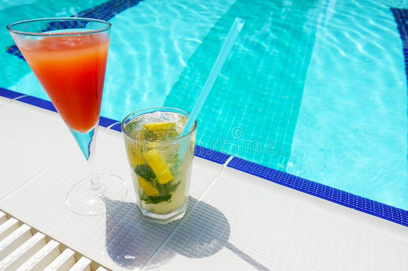 Two tasty cocktails near swimming pool on a hot summer day stock image