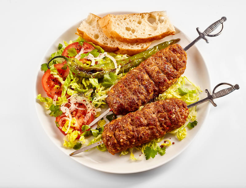Two tasty spicy Turkish adana lamb kebabs. Made with oak smoked young ground or minced meat on a long metal skewer served in a bed of fresh salad with bread stock images