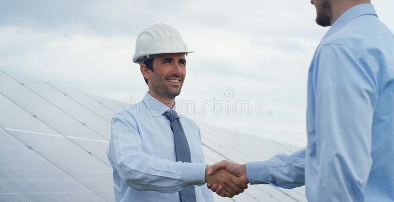 Two technical expert partners in solar photovoltaic panels, remote control performs routine operations to monitor the system using royalty free stock image