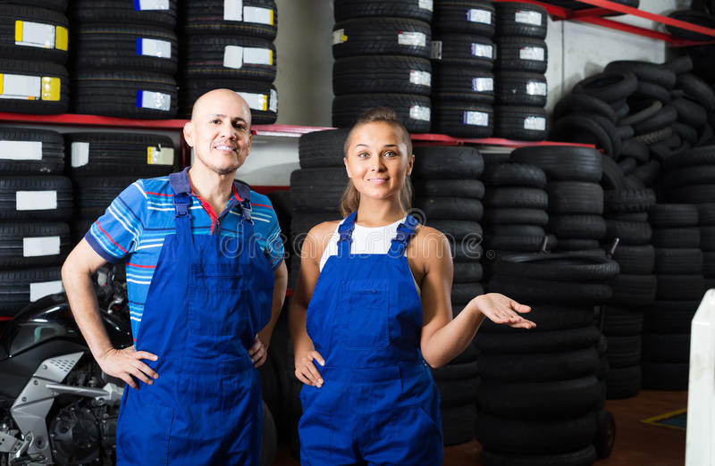 Two technicians in coveralls standing at car service point. Two cheerful european technicians in coveralls standing at car service point stock photo