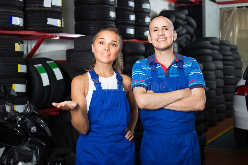 Two technicians in coveralls standing at car service point. Two happy technicians in coveralls standing at car service point royalty free stock images
