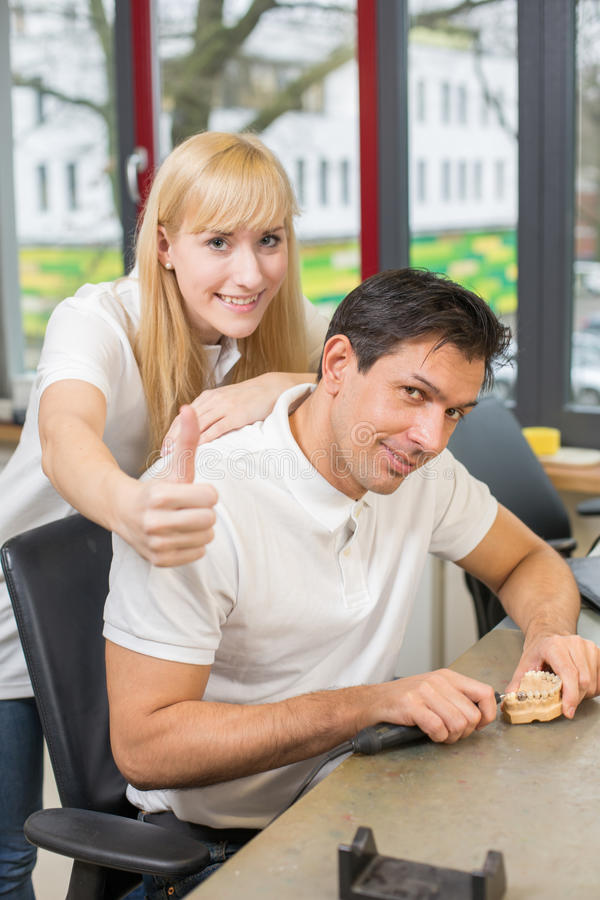 Two technicians in dental lab showing thumbs up royalty free stock photography