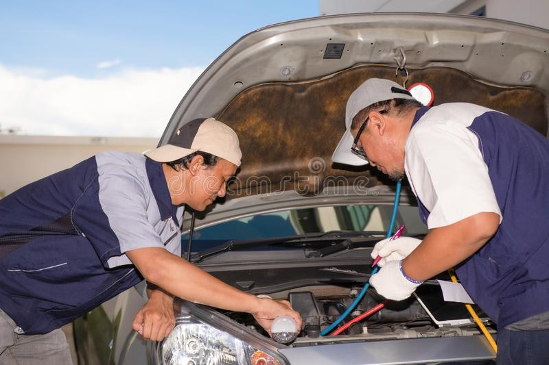 Two technicians are helping to check the car`s condition before royalty free stock photography