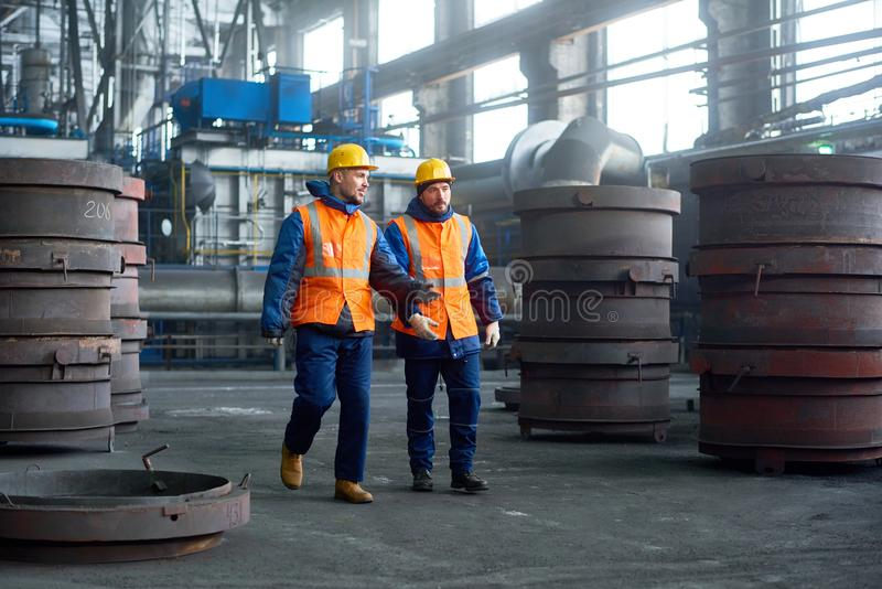 Two Technicians Walking Along Production Department. Team of hard-working technicians wearing hardhats and reflective vests walking along spacious production stock photography
