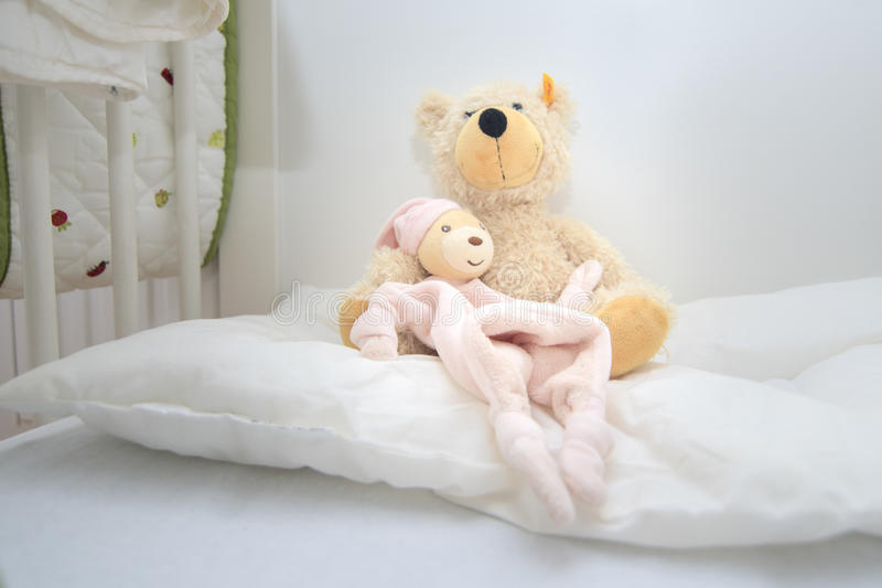 Two teddy bears in baby cott sitting on white pillow. Crib lovingly prepared by mother for the baby to be born stock images