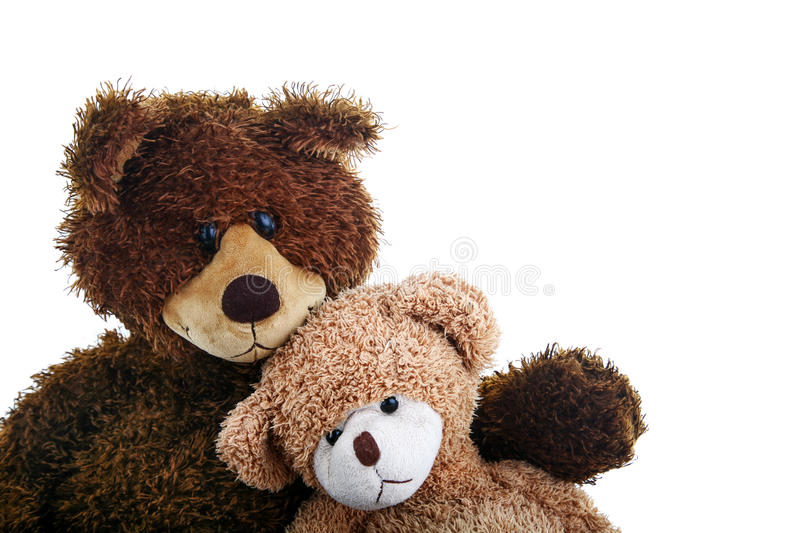 Two teddy bears, bigger and smaller, sitting close to each other like they are best friends. stock photo