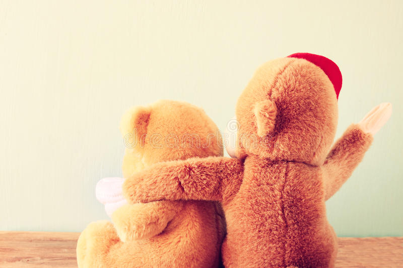Two teddy bears on a shelf with arms around each other. Retro vintage filter royalty free stock photos