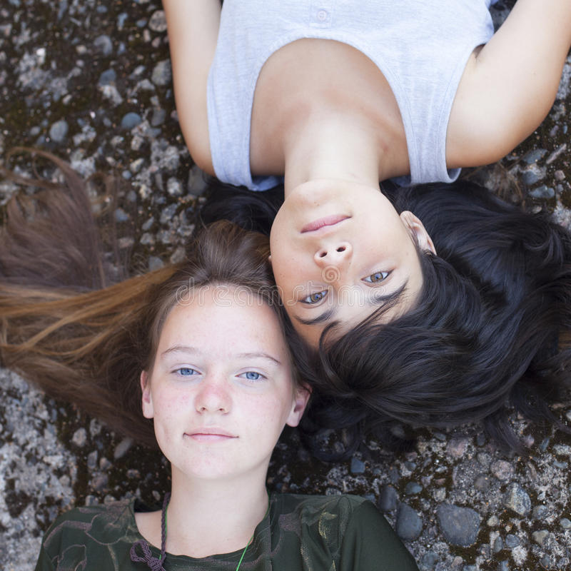 Two teen girl best friends lying on the rocks, top view. Outdoors. stock photos